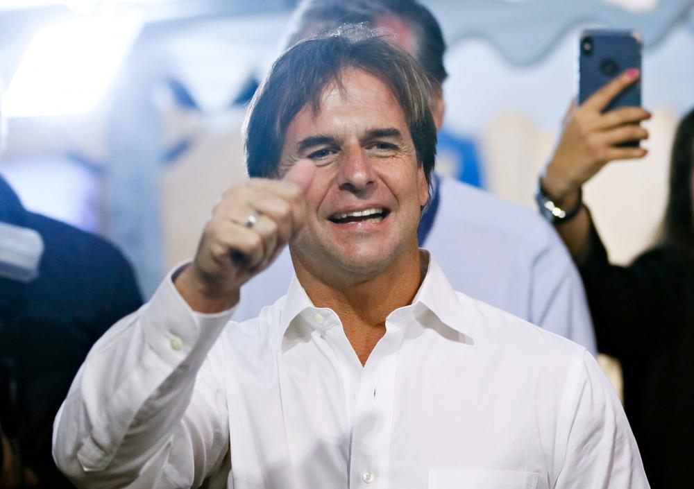 Luis Lacalle Pou, candidato do Partido Nacional, acena a correligionários enquanto espera resultado do segundo turno das eleições presidenciais do Uruguai neste domingo (24) - Foto: Mariana Greif/Reuters