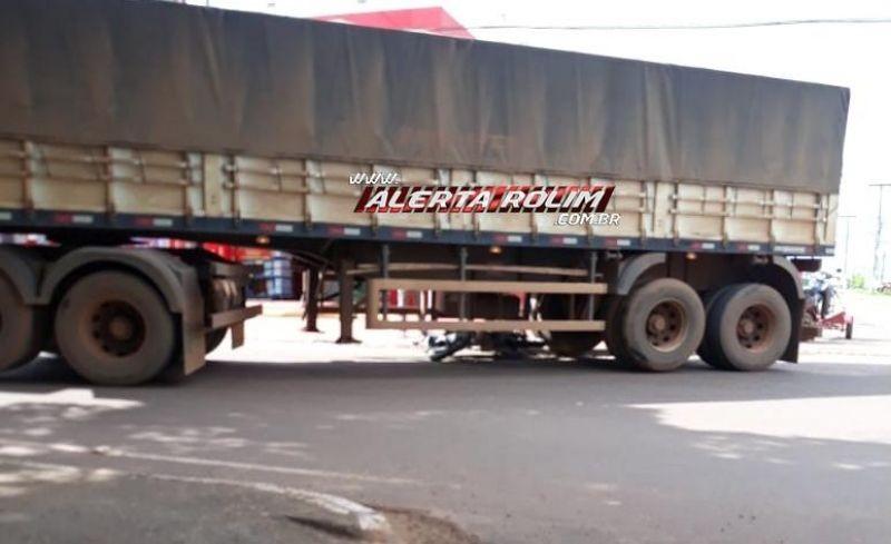 Moto fica debaixo de carreta após colisão no centro da cidade